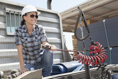 Mid adult woman holding a break hose of a flatbed truck Stock Photos