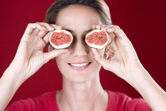 A mid adult woman holding figs up to her eyes Stock Photography