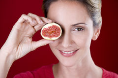 A mid adult woman holding half a fig in front of her eye Royalty Free Stock Image