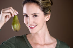 A mid adult woman holding a pear Royalty Free Stock Photos
