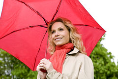 A mid adult woman holding a red umbrella Royalty Free Stock Image