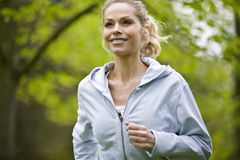 A mid adult woman jogging in the park Royalty Free Stock Photography