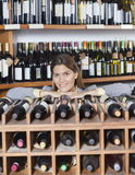 Mid Adult Woman Leaning On Wine Rack In Shop Royalty Free Stock Photography