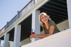Mid adult woman looking away while holding red wine glass in balcony at restaurant Stock Photography