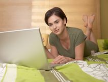 Mid-adult woman looking at computer in bed Stock Photo
