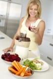 Mid Adult Woman Making Fresh Vegetable Juice Royalty Free Stock Photo