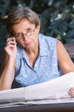 Mid adult woman with newspaper Royalty Free Stock Photography
