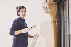 Mid adult woman paints the rooms of her house rooms royalty free stock photography