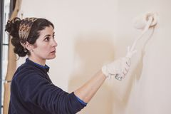 Mid adult woman paints the rooms of her house rooms stock image