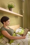 Mid-adult woman reading in bed Stock Photo