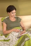 Mid-adult woman reading in bedroom Stock Image