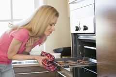 Mid adult woman removing baking tray from oven in kitchen stock image