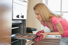 Mid adult woman removing baking tray from oven in kitchen. Mid adult women removing baking tray from oven in kitchen Stock Photography