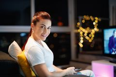 Hispanic Woman Sends Text Message Chats On Mobile Phone. Mid adult woman sitting on sofa at night, chatting with mobile phone. 40 years old latin american woman Stock Photography