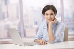 Mid adult woman smiling with computer. Mid adult woman sitting at office table with laptop computer, smiling at camera Stock Image