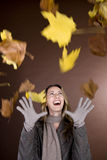 A mid adult woman smiling at falling autumn leaves stock images