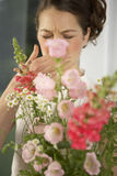 Mid adult woman sneezing behind a bouquet of flowers Royalty Free Stock Photos