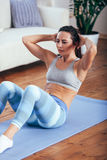 Mid adult woman training abdominals at home. Mid adult brunette woman wearing blue sportswear training abdominals at home Royalty Free Stock Photos