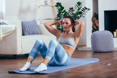 Mid adult woman training abdominals at home. Mid adult brunette woman wearing blue sportswear training abdominals at home Stock Photography