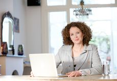 Mid adult woman using computer at home Stock Photo