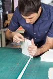 Mid Adult Worker Binding Pages At Table. Mid adult male worker binding pages at table in paper factory Royalty Free Stock Photo