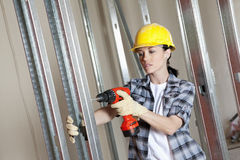 Mid adult worker drilling at construction site Stock Photography