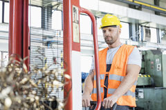 Mid adult worker pulling hand truck with steel shavings in factory royalty free stock photo