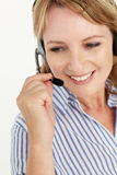 Mid age business women using headset. Mid age business woman using headset smiling off camera Royalty Free Stock Photography