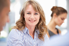 Mid age businesswoman in meeting. Smiling at camera Stock Photography