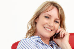 Mid age businesswoman using cellphone. Smiling at camera Royalty Free Stock Image
