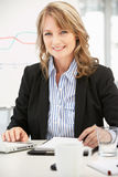 Mid age businesswoman at work Royalty Free Stock Images