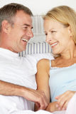 Mid age couple. In love lying on bed Stock Photos