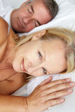 Mid age couple in bed Royalty Free Stock Photo