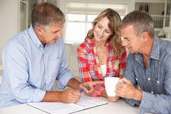 Mid age couple with financial advisor. At home stock photo