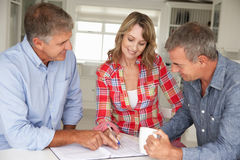 Mid age couple with financial advisor Royalty Free Stock Image