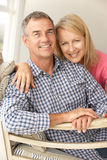 Mid age couple at home. Hugging and smiling Stock Photography