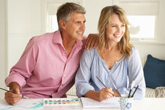 Mid age couple painting at home. Smiling Royalty Free Stock Photos
