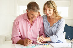 Mid age couple painting with watercolors Royalty Free Stock Photography