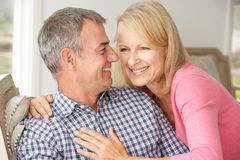 Mid age couple on sofa. Mid age couple at home on sofa smiling to each other Stock Photos