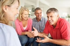 Mid age couples chatting at home Royalty Free Stock Photos