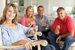 Mid age couples drinking together at home. Smiling at camera Stock Image