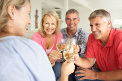 Mid age couples drinking together at home. Celebrating Royalty Free Stock Image