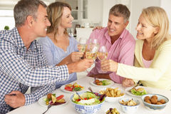 Mid age couples enjoying meal. At home smiling and laughing at each other Royalty Free Stock Photography