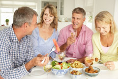 Mid age couples enjoying meal at home. Smiling and laughing Stock Image