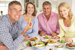 Mid age couples enjoying meal at home. Smiling at camera Stock Images