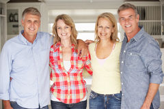 Mid age couples at home. Mid age couples relaxing at home smiling at camera Royalty Free Stock Image