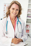 Mid age female doctor writing prescription. Smiling at camera Stock Images