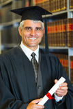 Mid age graduate. Cheerful mid age male law school graduate holding diploma Royalty Free Stock Image
