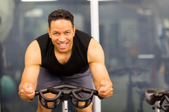 Mid age male cyclist. Handsome mid age male cyclist on gym bike Stock Images