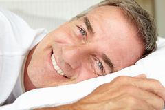 Mid age man in bed lying down Stock Photo